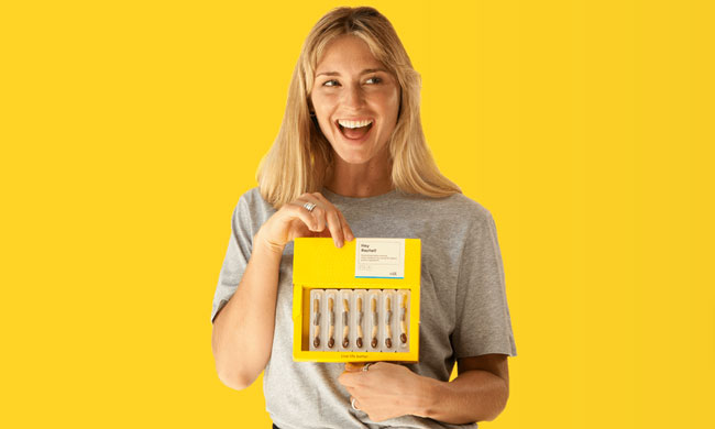 Vitl dna test in a woman's hand on a yellow background